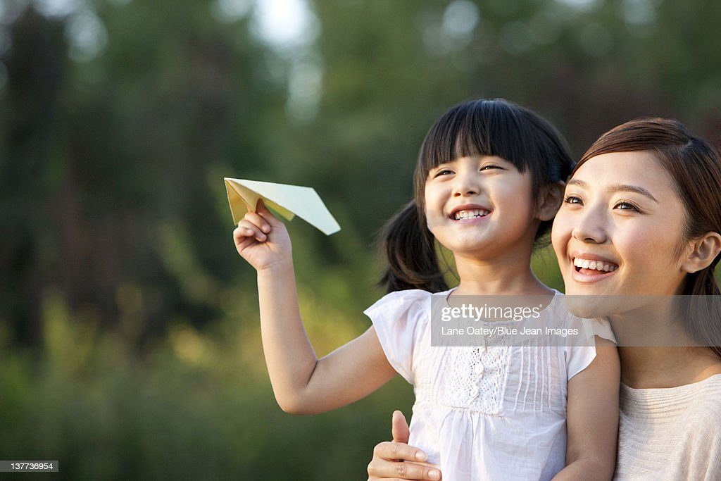 Young mother and daughter with a paper airplane : Stock Photo