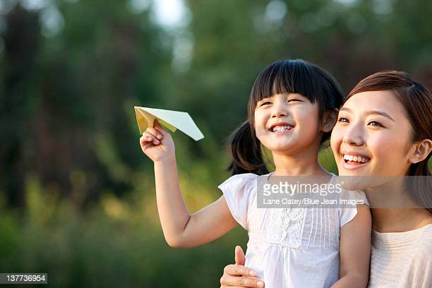 Young mother and daughter with a paper airplane