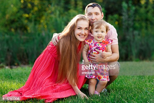 Young mother and father with small daughter on lawn : Foto de stock