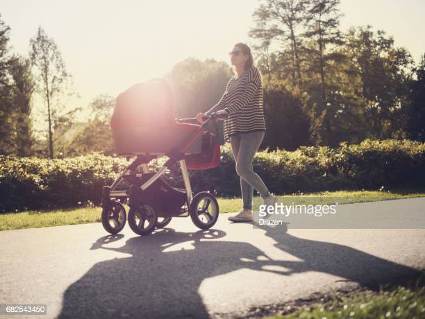 Young mother and her baby in baby carriage