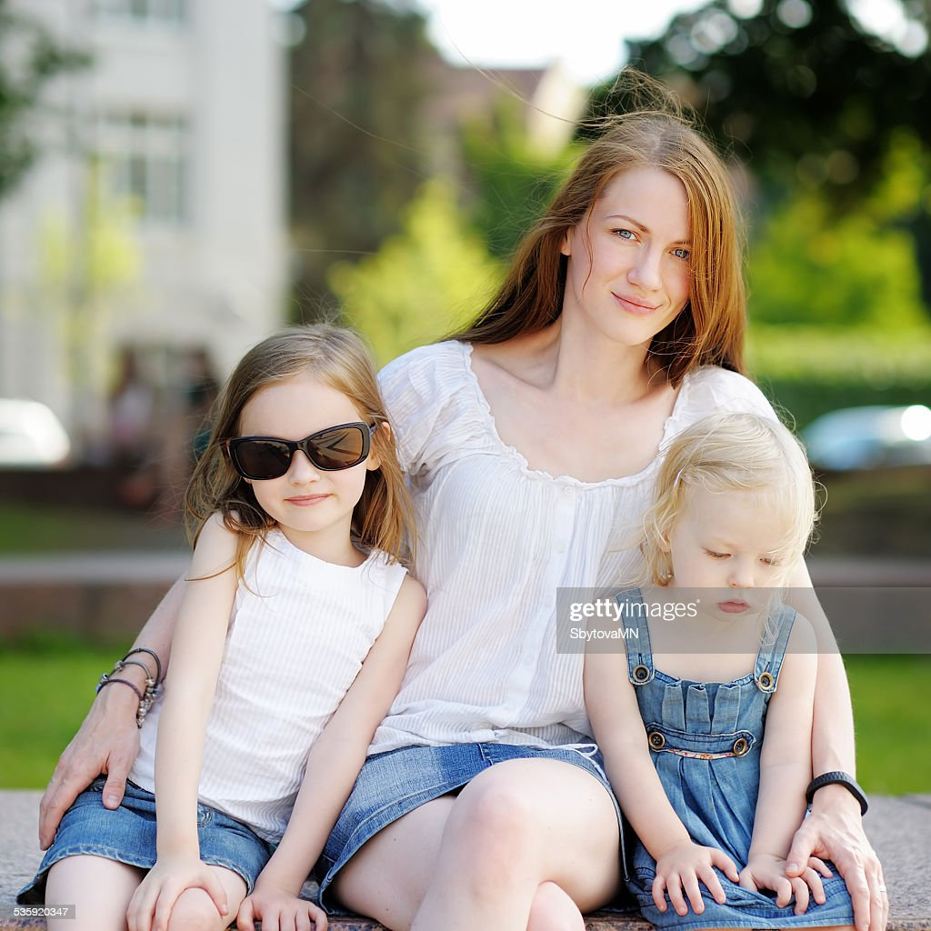 Young mother and her daughters outdoors : Stock Photo