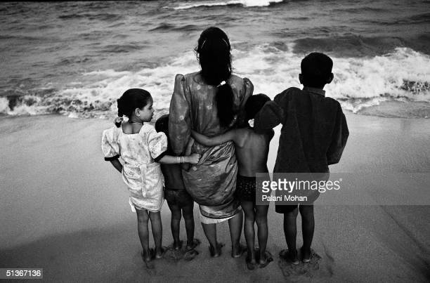 A young mother and her four children dip their toes in the surf as the sun goes down at Marina Beach in December 2003 in Madras India Marina's long...