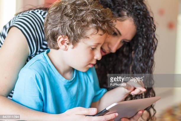 Jeune mère et son petit garçon à l'aide de tablette numérique
