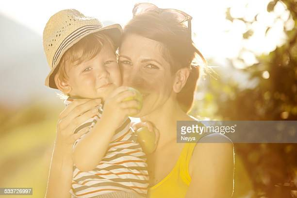 Young Mother and her Son Holding Apples