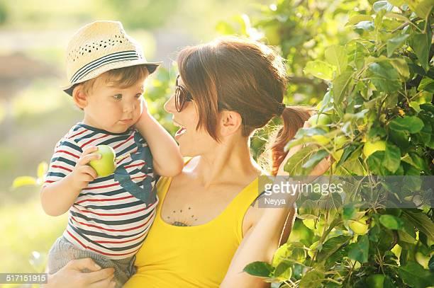 Jovem mãe e seu filho Apanhar Frutos de Maçã