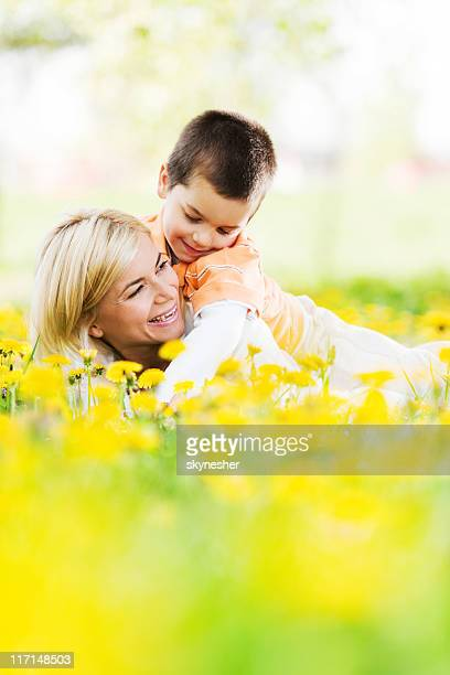 Young mother and her son playing in field of dandelions.