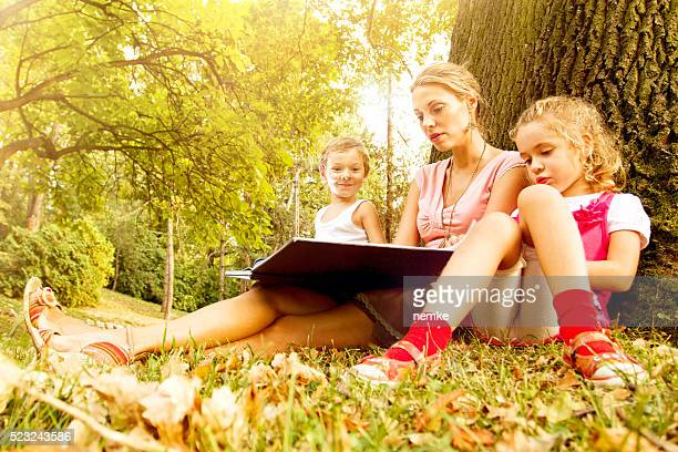 Young mother and her two kids reading together