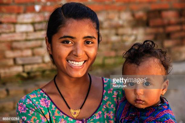 Young mother carrying her baby, Bhaktapur, Nepal