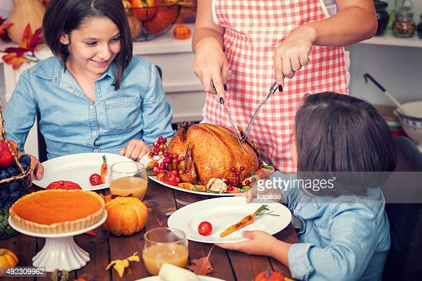 Young mother carving thanksgiving turkey