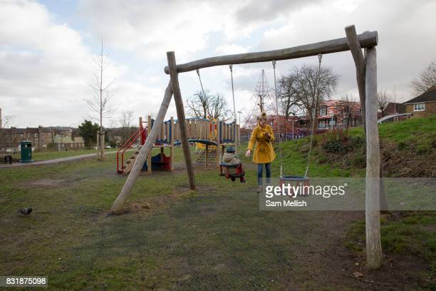 A young mother checks her mobile phone whilst pushing child on a swing on 11th January 2017 in London United Kingdom West Norwood community...