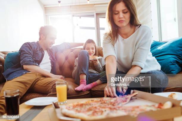 young mother cutting a slice of pizza