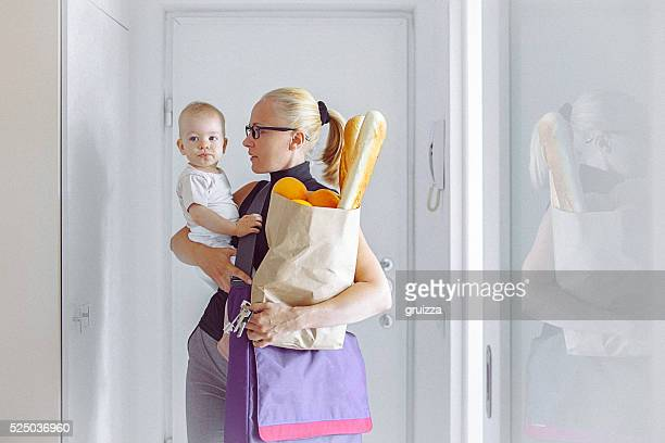Young mother enters home, carrying her baby and grocery bag