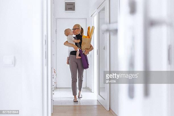 Jovem mãe introduz casa, levar o seu bebé e saco de mercearia