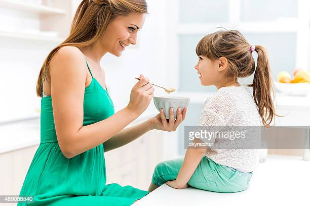 Young mother feeding her daughter in the kitchen.
