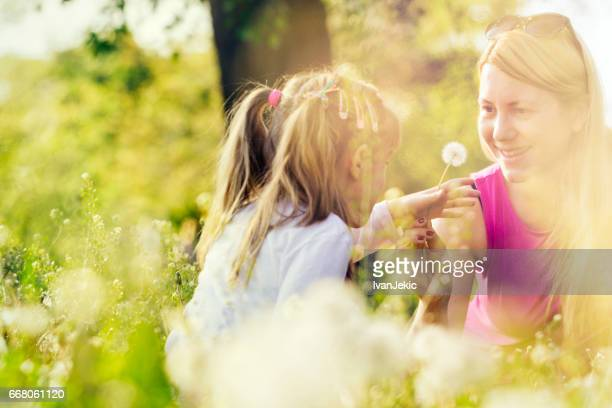 Young mother giving a dandelion flower to her daughter