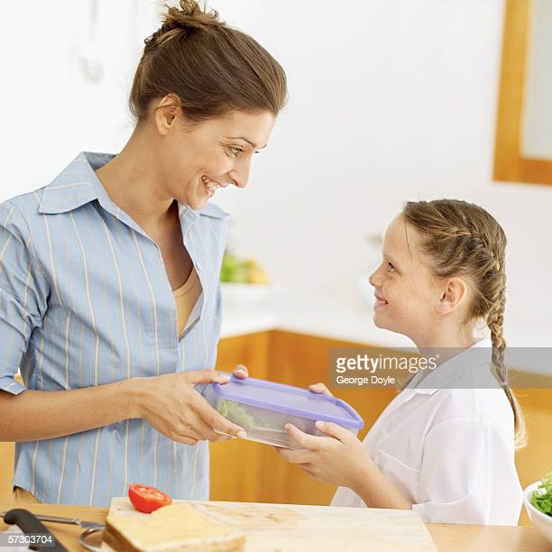 Young mother giving a young girl (8-10) her lunch box