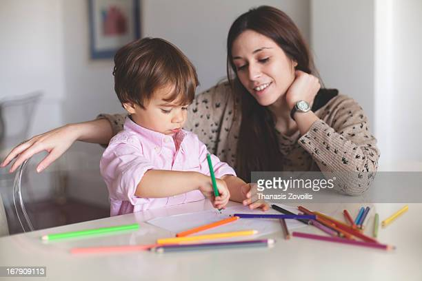 Young mother helping her son with drawing