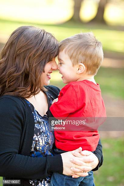 Young mother holding son at the park while they smile