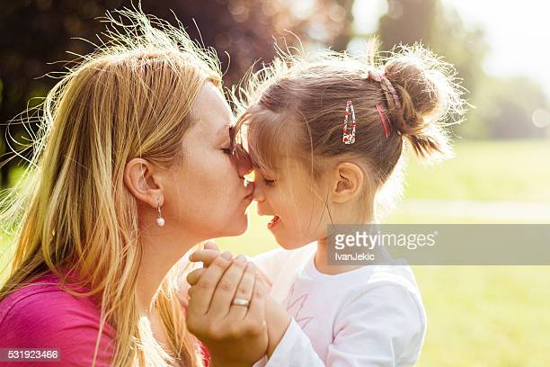 Young mother hugging and kissing her daughter in nature