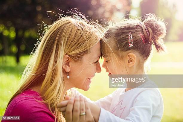 Joven madre abrazando a su hija en la naturaleza