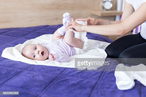 Young mother is changing diapers to her baby girl
