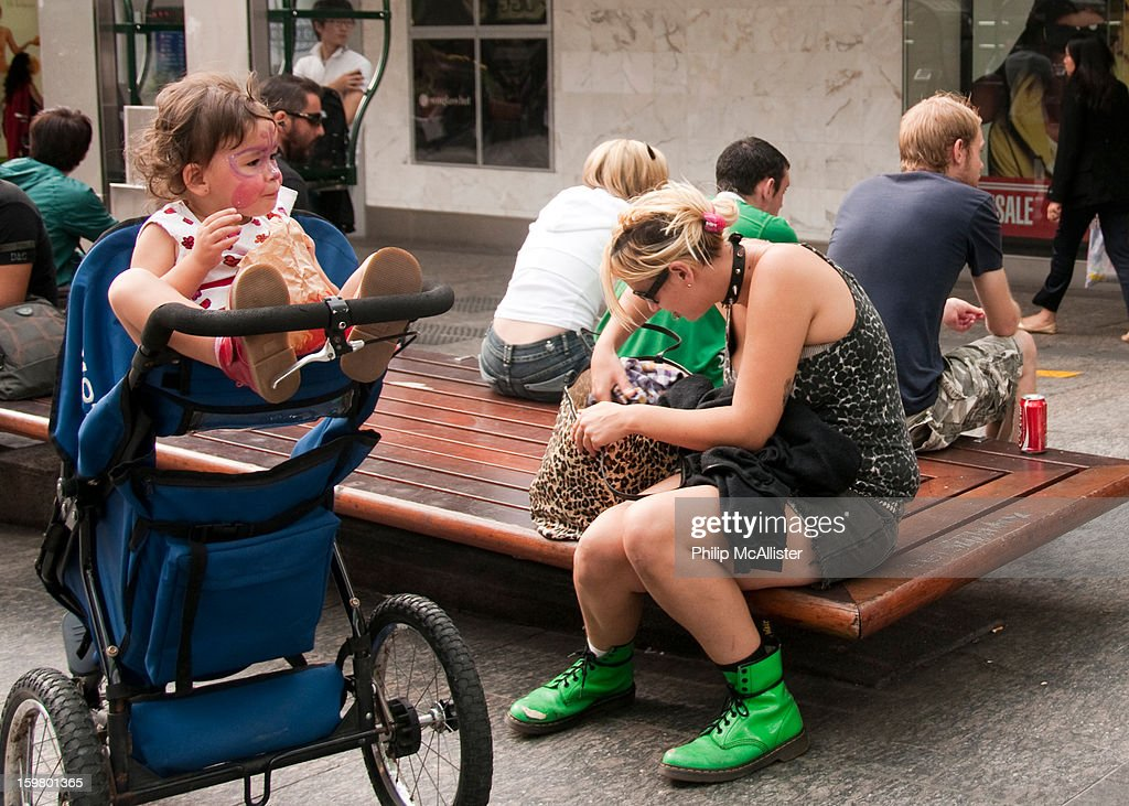 CONTENT] A young mother is dressed punk style with studded dog collar and leopard print top.She is searching in a plastic leopard print bag.Her baby has a painted face.The mother is also wearing bright green boots.