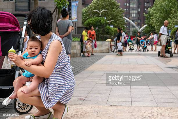 A young mother is feeding her baby in a residential community China is considering whether to allow all couples to have a second child because a...