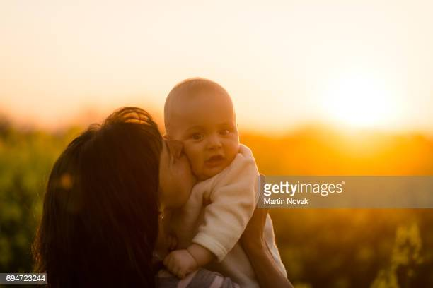 Young mother kissing her tot. Nature background.