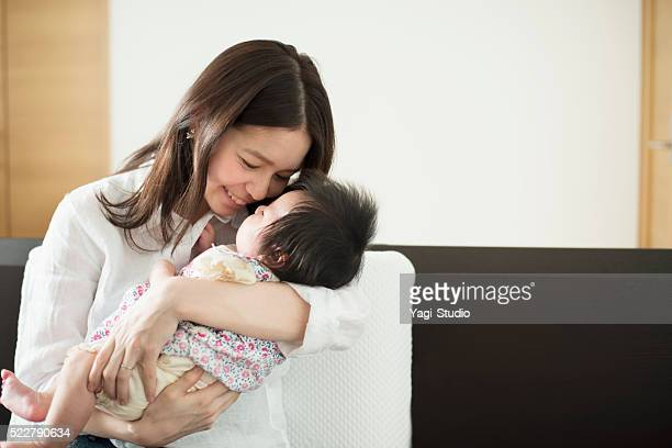 Young mother loving her baby girl at home