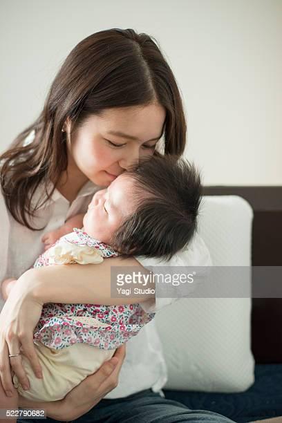 Liebevolle junge Mutter Ihr Babymädchen wie zu Hause fühlen.