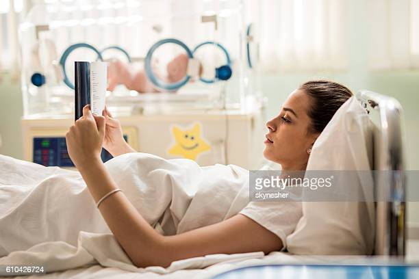 Young mother lying in maternity bedroom and reading a book.