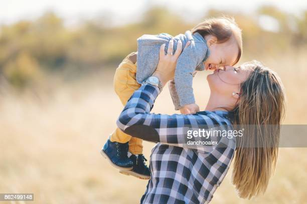 Young mother outdoors kissing her baby boy