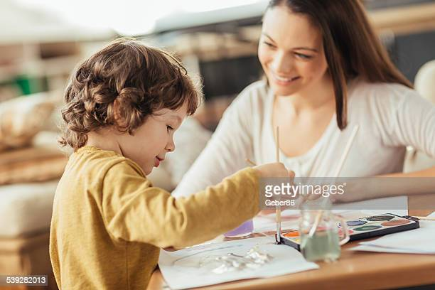 Young mother painting with son