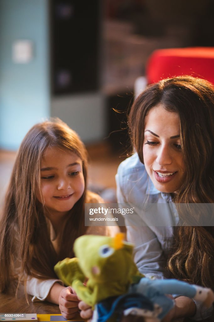 Young mother playing with her daughter and a puppet : Stockfoto