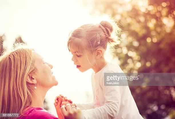 Joven madre jugando con su hija en la naturaleza