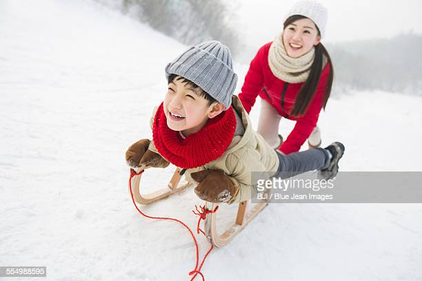 Young mother pulling son on sled
