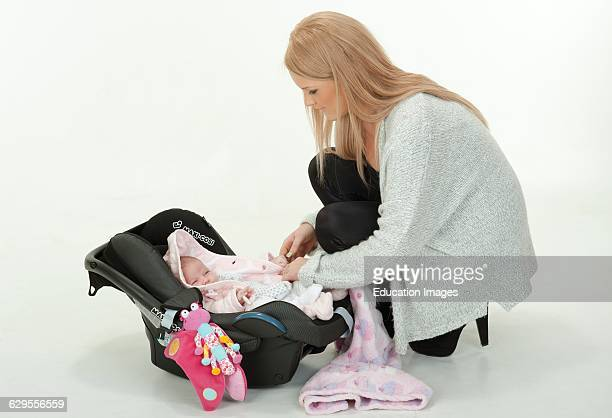 Young mother putting her 4 week old baby girl into a car seat