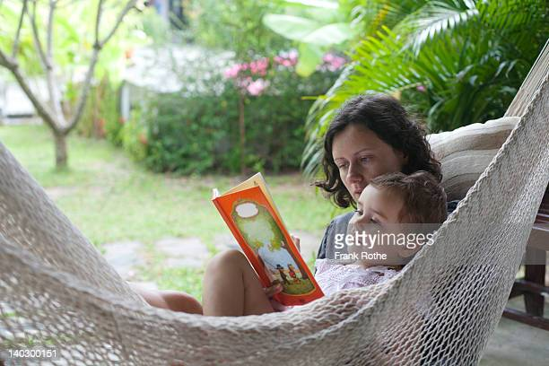 young mother reads a book to here daughter