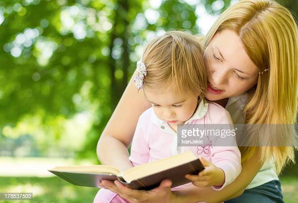 Young mother reads book with her daughter