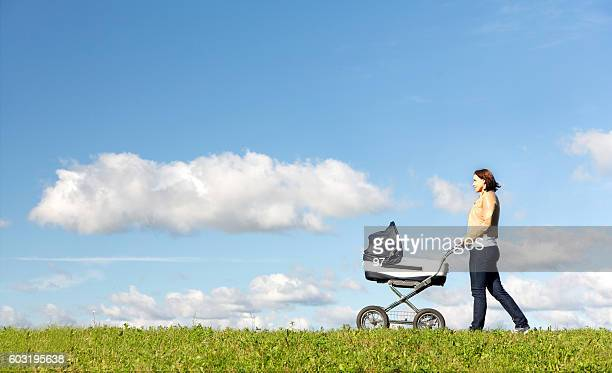 Young mother running while pushing a stroller on meadow