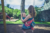 A young mother is sitting on a sling in the playground with her baby in a sling