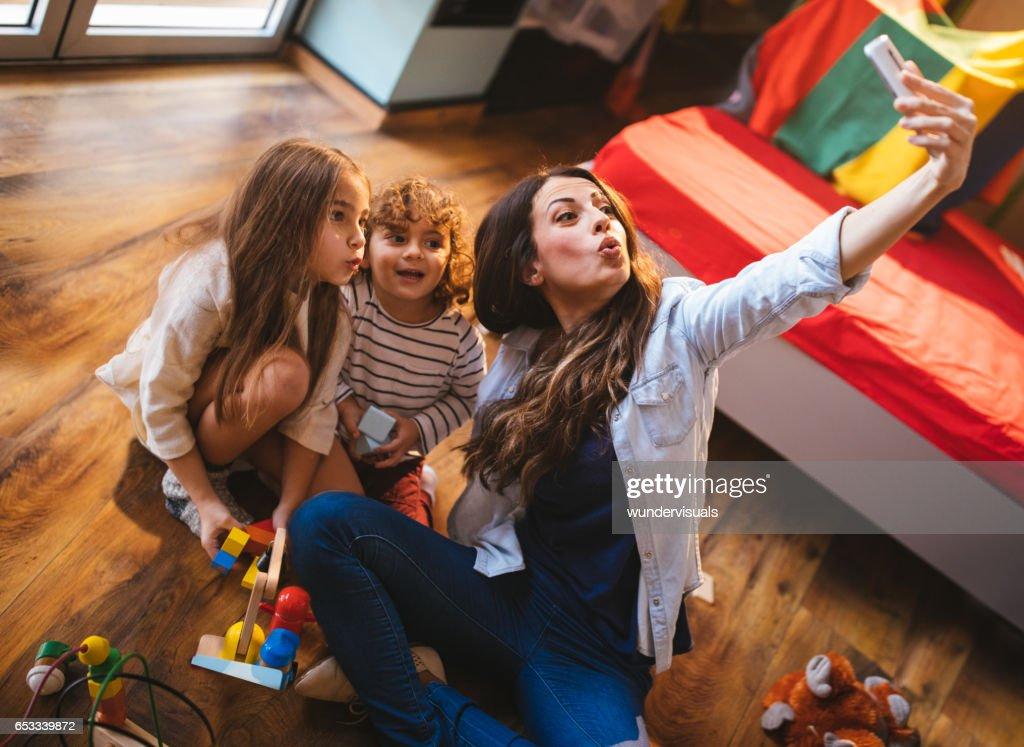 Jeune mère tenant un selfie avec son fils et sa fille : Photo