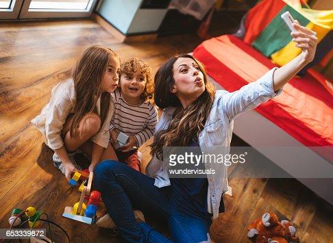 若い母親が彼女の息子と娘と一緒に、selfie を取って : ストックフォト