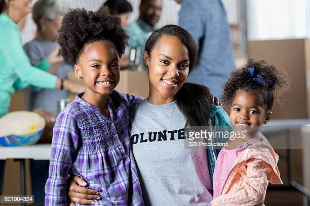 Young mother volunteers with daughters during food drive