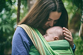 A young mother with a baby in a sling is walking in the tropical forest