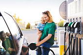 Young mother with baby boy at the petrol station refuelling the car.