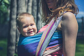 A young mother is standing outside with her baby in a sling