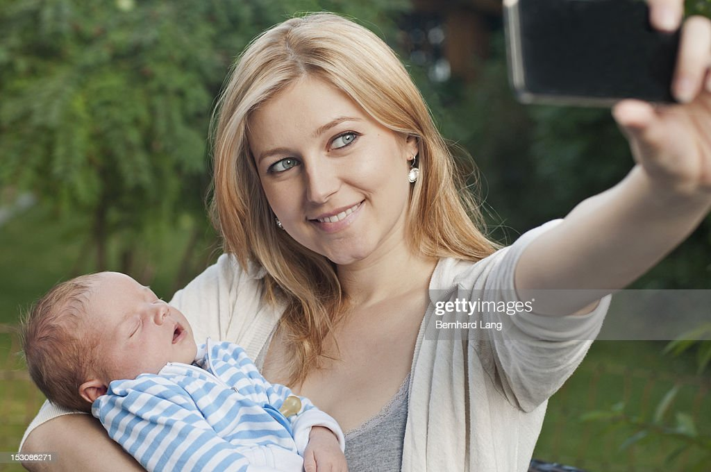 Young mother with baby using smartphone : Stock Photo