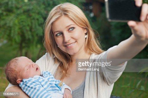 Young mother with baby using smartphone : Bildbanksbilder