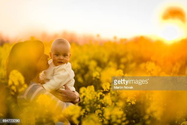 Young mother with her baby spending time in the rapeseed field